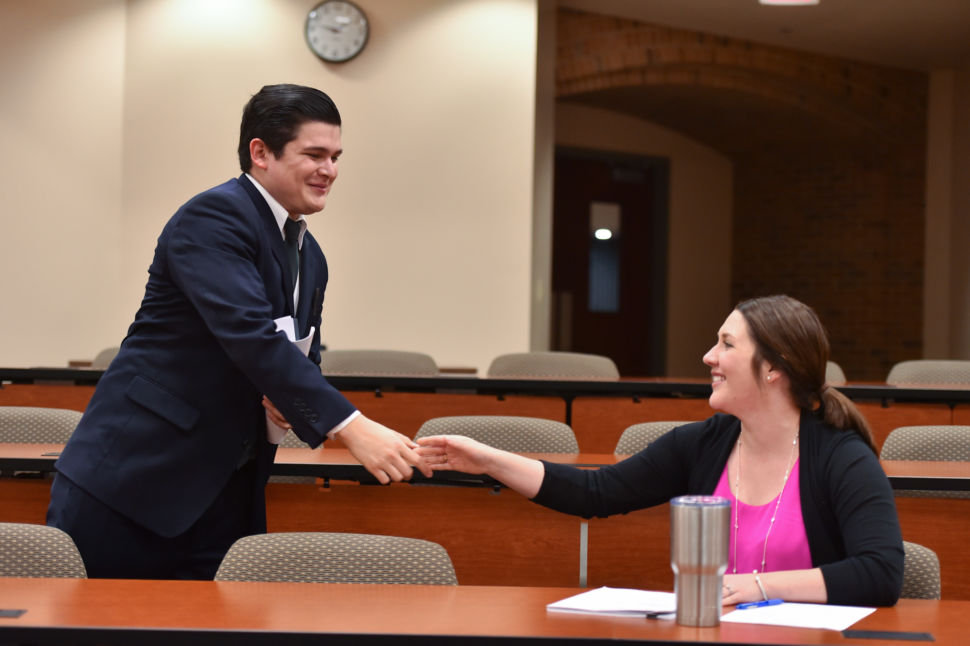 Two law students shaking hands in a classroom