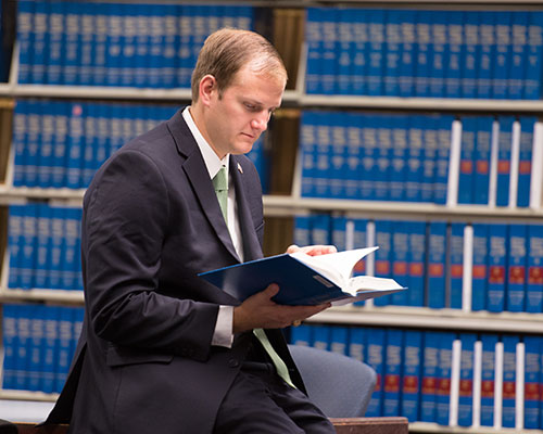 A student in a suit reads a book, with large bookcases full of law books in the background