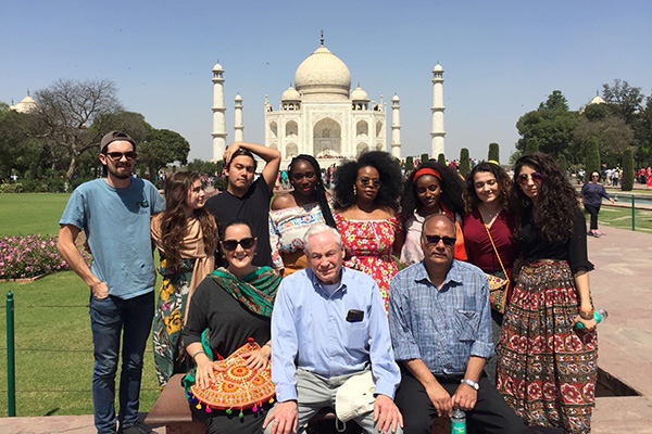 A group of students and faculty smile in front of the Taj Mahal